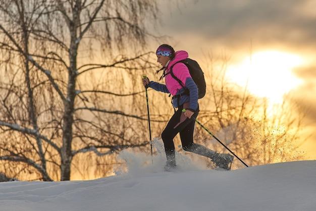 Una joven deportista corre con raquetas de nieve.