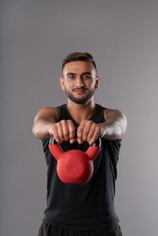 Joven deportista entrenando con pesas rusas