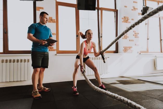 Joven deportista es ejercicios en gimnasio con entrenador