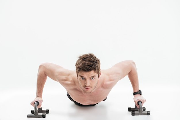 Joven deportista en forma haciendo flexiones con barras