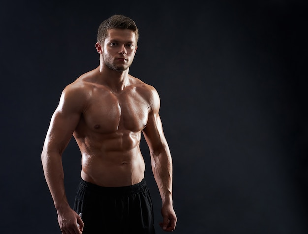 Joven deportista en forma muscular posando sin camisa sobre fondo negro