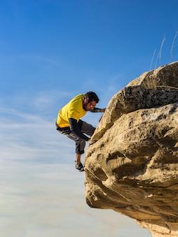 Joven deportista guapo subiendo un acantilado de roca