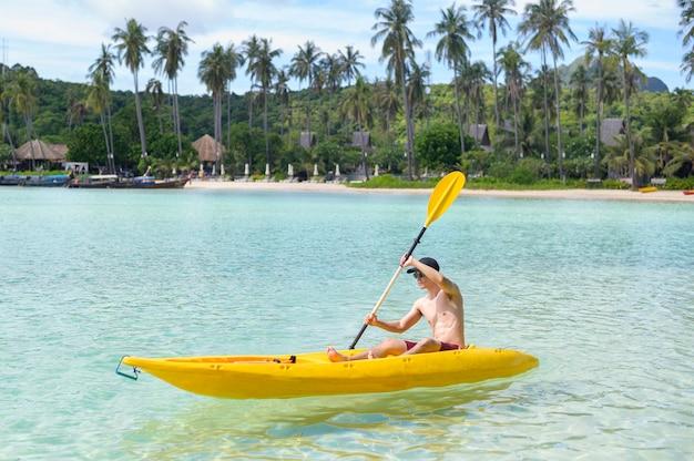 Un joven deportista en kayak en el océano en un día soleado