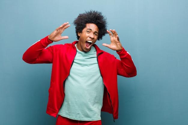 Joven deportista negro gritando de pánico o ira, sorprendido, aterrorizado o furioso, con las manos al lado de la cabeza