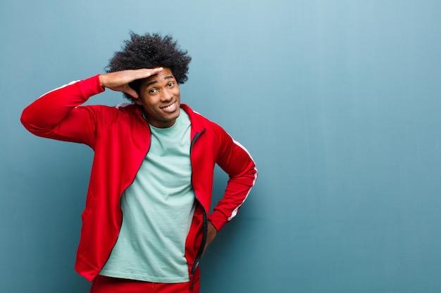 Joven deportista negro mirando desconcertado y asombrado, con la mano sobre la frente mirando a lo lejos, mirando o buscando en la pared del grunge