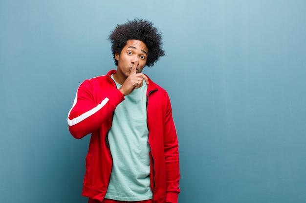 Joven deportista negro pidiendo silencio y silencio, haciendo un gesto con el dedo delante de la boca, diciendo shh o guardando un secreto contra el grunge