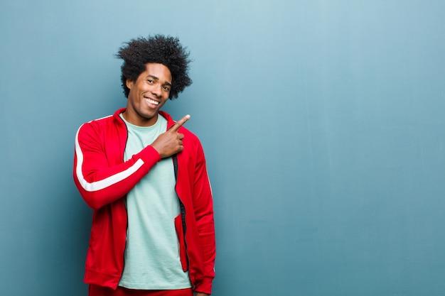 Joven deportista negro sonriendo alegremente, sintiéndose feliz y apuntando hacia un lado y hacia arriba, mostrando el objeto en el espacio de la copia contra la pared del grunge