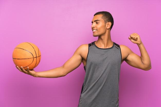 Joven deportista con pelota de baloncesto sobre pared púrpura aislado celebrando una victoria