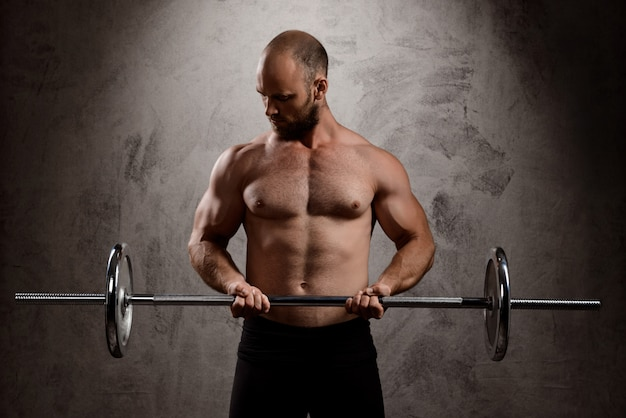 Joven deportista poderoso entrenamiento con barra sobre la pared oscura.