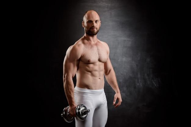 Joven deportista poderoso entrenamiento con pesas sobre pared negra.