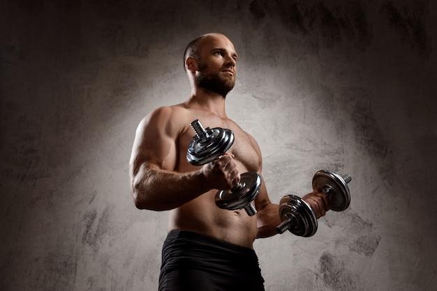 Joven deportista poderoso entrenamiento con pesas sobre la pared oscura.
