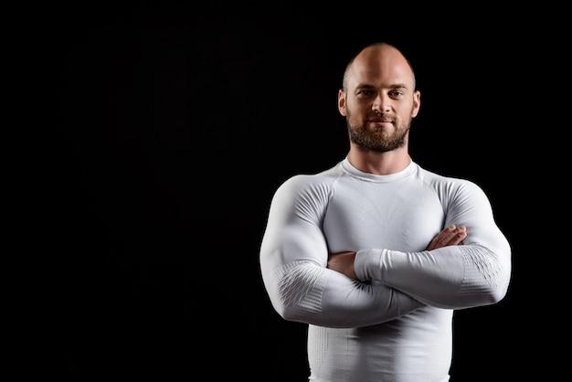 Joven deportista poderoso en ropa blanca sobre pared negra.