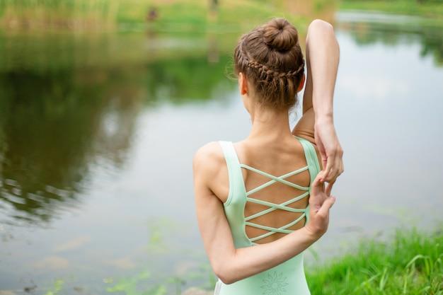 Una joven deportista practica yoga en un césped verde junto al río, el yoga ataca la postura. meditación y unidad con la naturaleza.