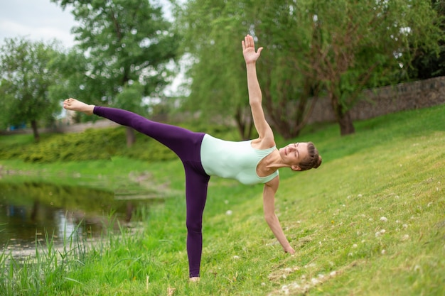 Una joven deportista practica yoga en un césped verde junto a la postura de asana de yoga del río