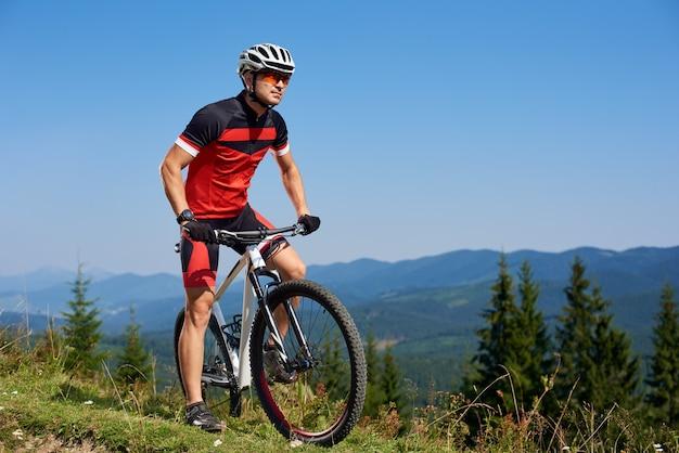 Joven deportista profesional atlético comenzando bicicleta de ciclismo en la cima de la colina