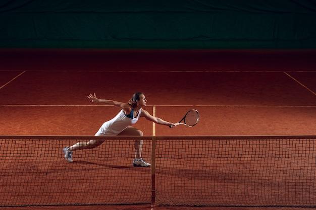Joven deportista profesional caucásica jugando al tenis en la pared de la cancha deportiva.