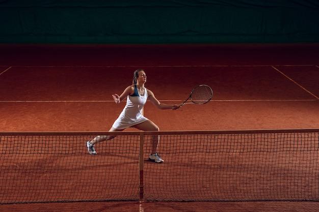 Joven deportista profesional jugando al tenis en la pared de la cancha deportiva