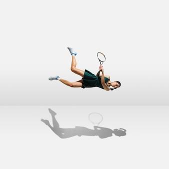 Joven deportista profesional levitando volando mientras juega al tenis aislado en la pared blanca