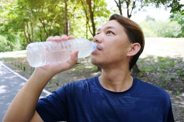 Joven deportista en ropa deportiva de color azul marino, descansando y bebiendo agua