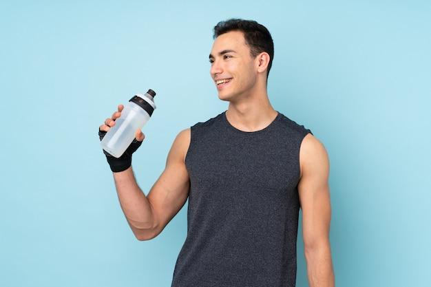 Joven deportista sobre pared azul con botella de agua deportiva