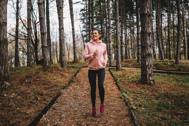 Joven deportista sonriente con hábitos saludables corriendo en el bosque en otoño y preparándose para el maratón.