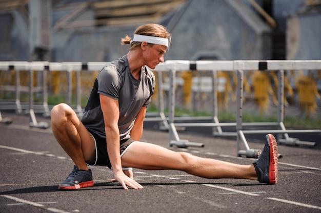 Joven deportista trabajando, estirando antes de correr