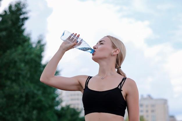Joven deportiva bebiendo agua inmóvil de una botella.