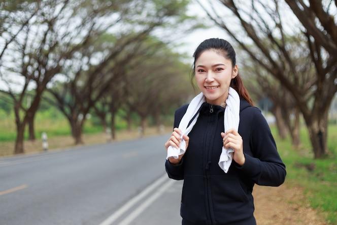 Joven deportiva con toalla blanca descansando después de ejercicio deportivo ejercicios al aire libre en el parque