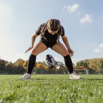 Joven deportiva dejando caer una pelota de rugby