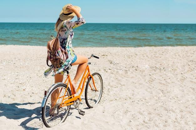 Joven deportiva en elegante top blanco y pantalones cortos de mezclilla de pie en la playa con bicicleta naranja
