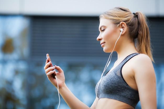 Joven deportiva escucha música a través de un teléfono inteligente y auriculares