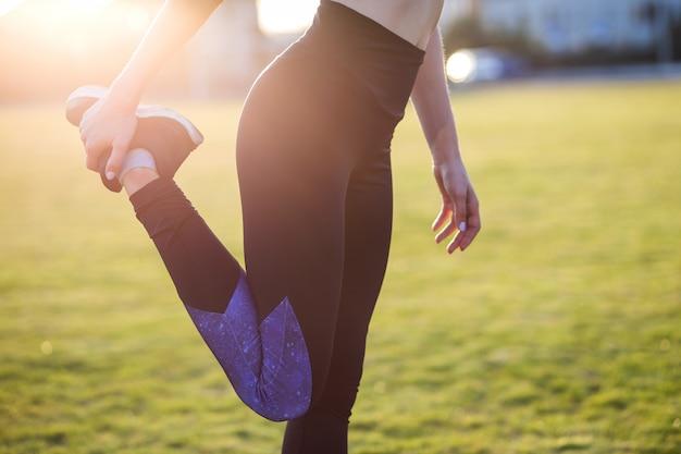 Joven deportiva haciendo ejercicio antes de correr en el campo de la mañana al aire libre