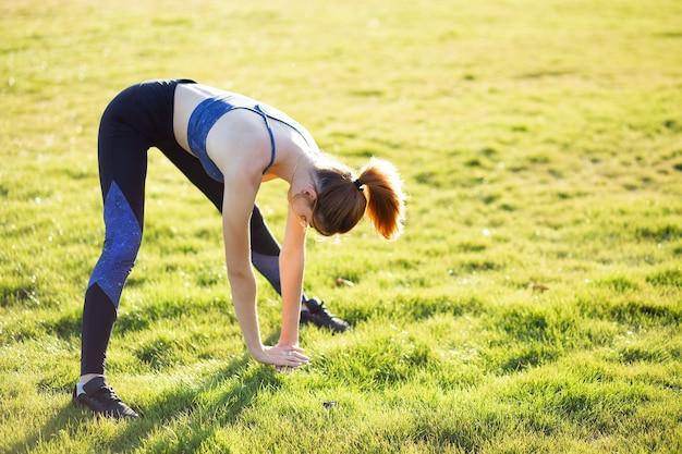 Joven deportiva haciendo ejercicios de fitness en la hierba verde en un día caluroso de verano al aire libre