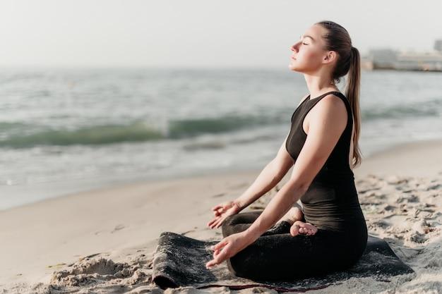 Joven deportiva practica yoga meditación en la playa cerca del océano