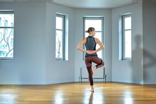 Joven deportiva practicando yoga, ejercicio, vistiendo ropa deportiva, pantalones y top, interior de cerca, estudio de yoga. vista trasera