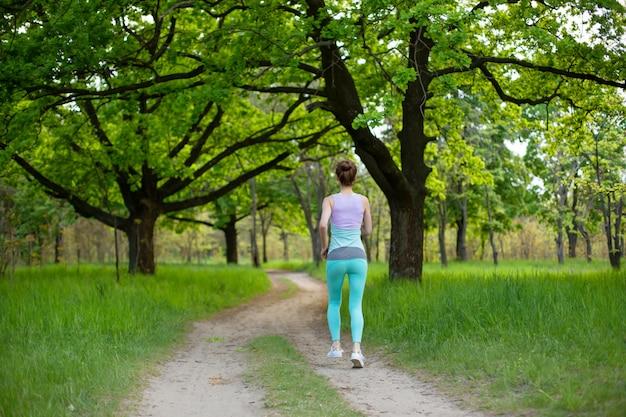 Una joven deportiva que se ejecuta en un bosque de verano verde abandonado. deporte y bienestar