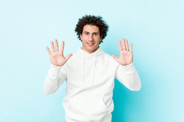 Joven deportivo contra una pared azul que muestra el número diez con las manos.