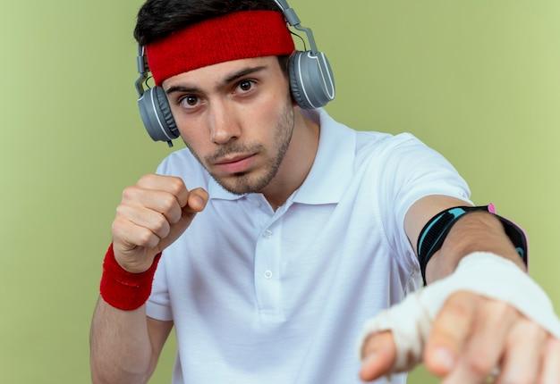 Joven deportivo en diadema con auriculares y brazalete de teléfono inteligente posando como un luchador con el puño cerrado sobre verde