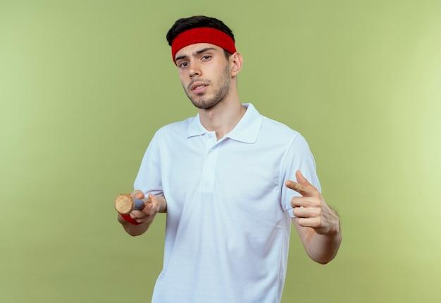Joven deportivo en diadema sosteniendo un bate de béisbol apuntando con el dedo a cemera mirando confiado de pie sobre la pared verde
