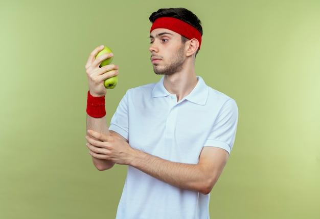 Joven deportivo en diadema sosteniendo dos manzanas verdes mirándolos con cara seria sobre verde