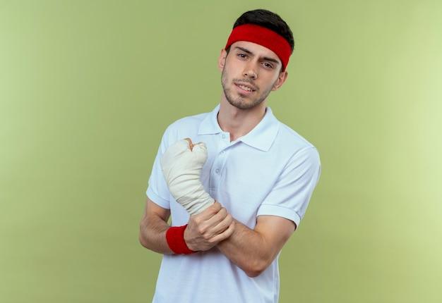 Joven deportivo en diadema tocando su muñeca vendada sintiendo dolor sobre verde