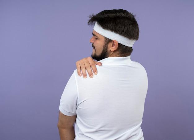 Joven deportivo de pie detrás de la vista con diadema y muñequera agarró el hombro dolorido