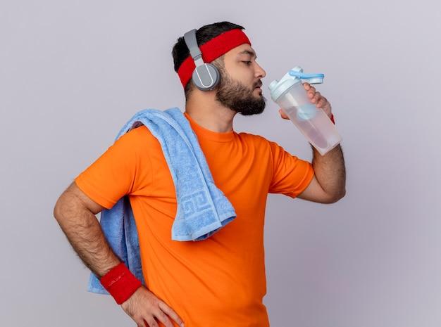 Joven deportivo de pie en la vista de perfil con diadema y muñequera con auriculares bebe agua de una botella de agua poniendo la mano en la cadera con una toalla en el hombro aislado sobre fondo blanco.