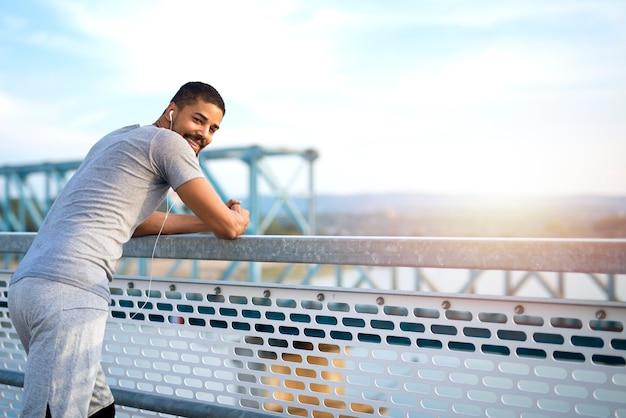 Joven deportivo en el puente con un descanso