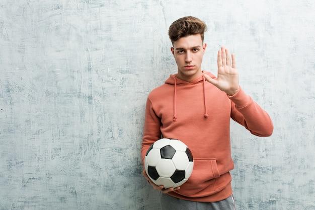 Joven deportivo sosteniendo una pelota de fútbol de pie con la mano extendida que muestra la señal de stop, evitando que