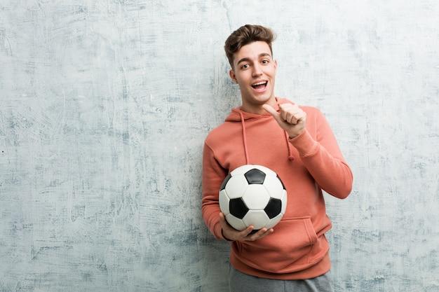 Joven deportivo sosteniendo una pelota de fútbol sonriendo alegremente señalando con el dedo lejos