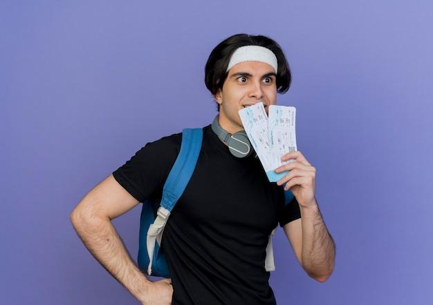 Joven deportivo vistiendo ropa deportiva y diadema con mochila sosteniendo billetes de avión mirando a un lado sonriendo sorprendido