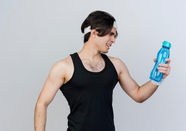 Joven deportivo vistiendo ropa deportiva y diadema sosteniendo una botella de agua mirándolo confundido de pie sobre la pared blanca