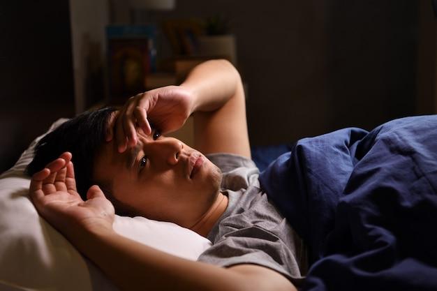 Un joven deprimido que sufre de insomnio acostado en la cama