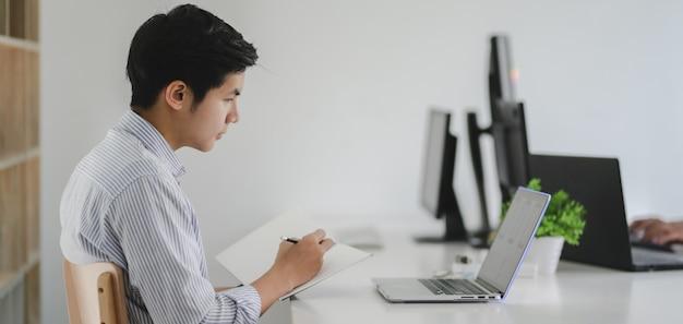 Joven desarrollador web profesional de iu trabajando en su proyecto con una computadora portátil